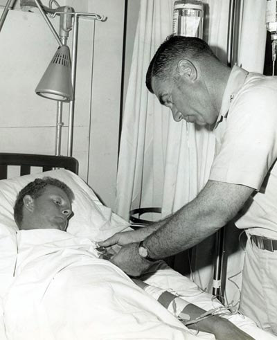 A2C Davis, Lyle K., AF14861942 wounded in action on 4 Dec 1966, is being presented the Purple Heart at U. S. Army 3rd Field Hospital by Col Grover K. Coe, Tan Son Nhut's Base Commander.