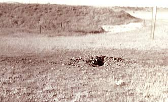 Photo Right, by Paul Huff, 6251st SPS:122mm crater, taken AUG 1 '72, 150 feet or so behind Bullseye-7 in Bomb Alley (north perimeter), just missing a revetment full of 500 pounders.