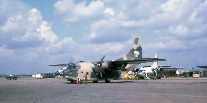 Bien Thuy Air Base flight line. C-123 prepares to start second engine, as crewman standsby with extinguisher. MSgt Summerfield: 12