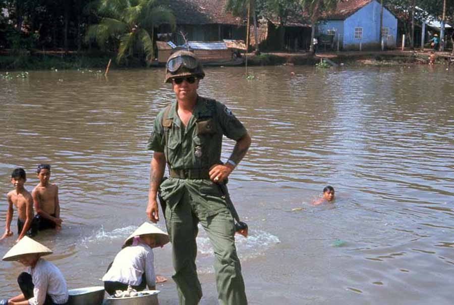 Bien Thuy Air Base. Mamasan do washie-clothes while kids swim. MSgt Summerfield, 1968: 06