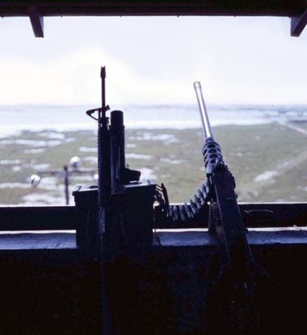 4. Cam Ranh Bay AB. Perimeter Tower view. M-16 and .50-Cal on the counter. Floodlights (foreground) illuminate the marsh and shore. 1970. Photo by: Jim Randall, LM 69, CRB, 483rd SPS, 1970.