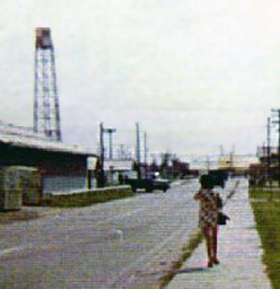 20. Cam Ranh Bay AB, Vientmaese civilian walking to work. Did you notice here dress-pattern matches the Water Tower is on the left? 1972-1973. Photo by: Steve Ray, LM 304, CRB, 483rd SPS; KRT, 388th SPS. 1972-1973.