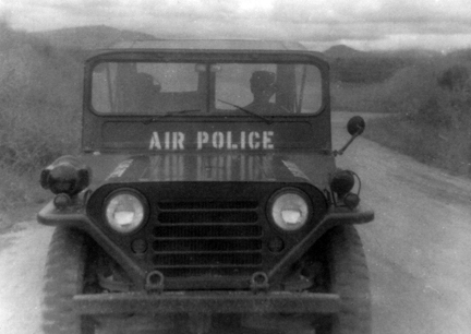 6. Da Nang AB: SSgt Coleman driving an AP jeep. 35th APS Jeep, bomb dump perimeter road. 1965.