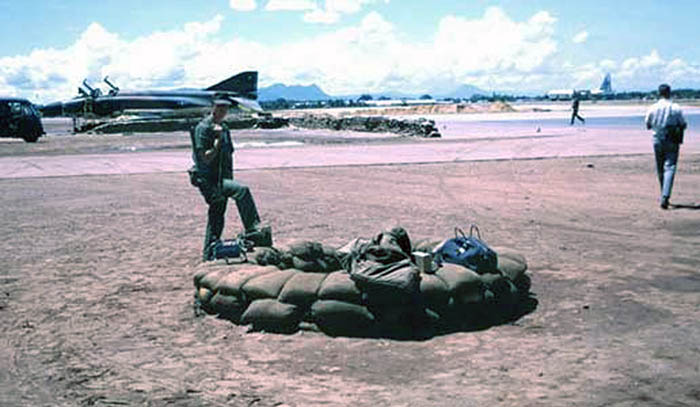 3. Da Nang AB, 366th SPS. SP Post. No where to hide from a blistering sun. When the rains come, the fighting-hole will fill with water. Last of the old sandbag revetments visible for F-4 Phantom parking. Photo by: James Paul Mashburn 1966-1967.