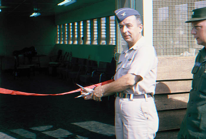 19. Da Nang AB, Tent City: Base Commander, Colonel Eisenbrown cuts red dedication ribbon, officially opening the Day Memorial Room. 1966.