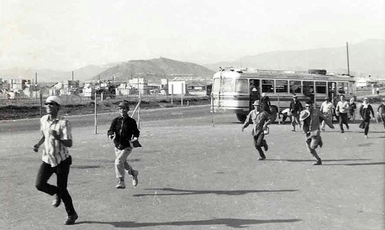 12. Nui Dat: Civilian Vietnamese workers running to work frombus. Photo by Dana Anthony, ND 1969.