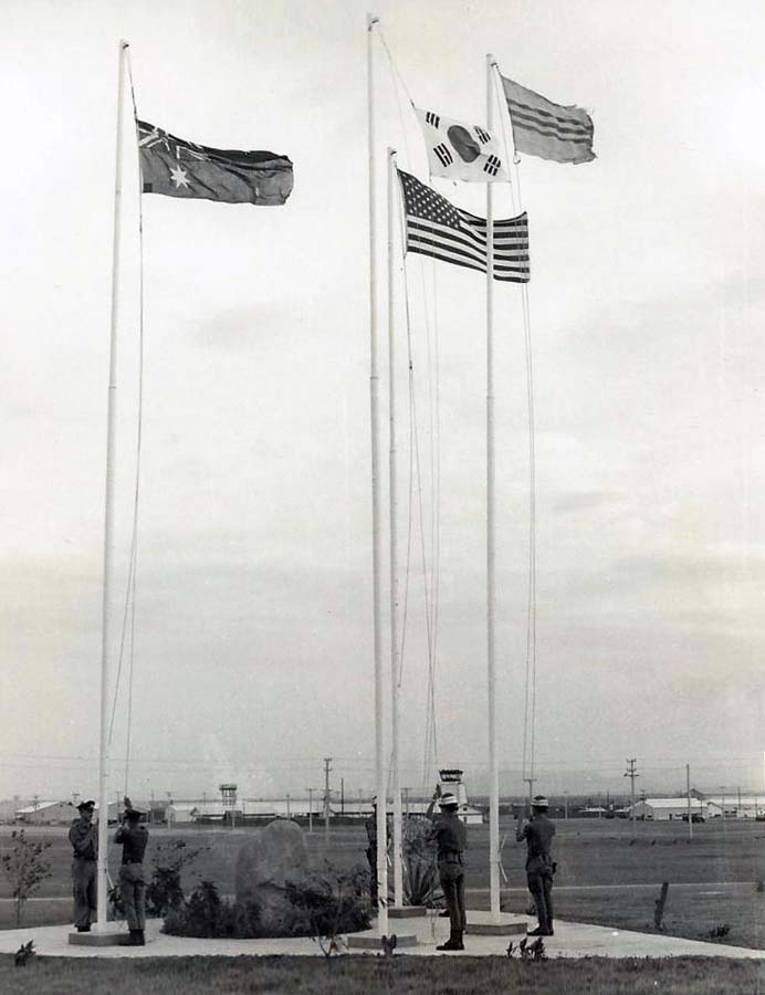 13. Nui Dat: Australian Base. Allied troops raise national flags. Photo by Dana Anthony, ND 1969.