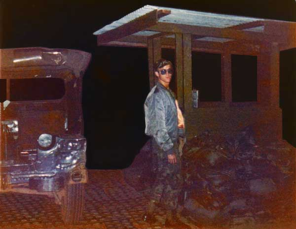 3. NKP flight line Entrance Gate, April 1975: Sgt Bacon is in front of the gate standing next to my jeep. I didn't send it earlier because I took it at night and it's very dark. Photo by: Jonathan Faulkner, 56th SPS, NKP.