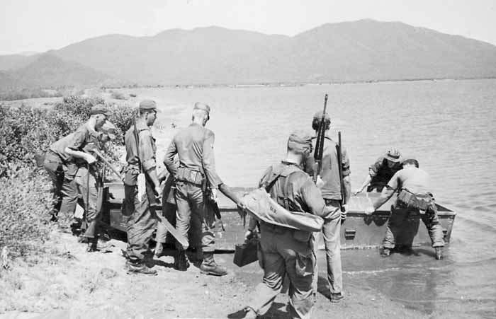 Photo #1 (Nha Trang): This is a shot of several of us getting ready to cross the river in order to get to the firing range. I am the tall one wearing the Ridgeway Hat with back to camera. I remember that me and another AP had to swim the river to retrieve the boat. While we were firing, someone had returned to boat to the pier, leaving us stranded. The two APs pictured holding the rear of the boat are; facing and in tiger stripes, Ken Kirchner and the AP with his back to the camera is Earl Mercer.