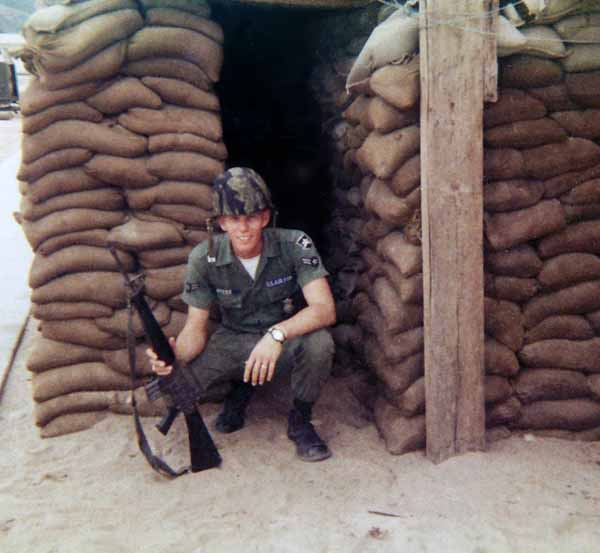 Photo #11 (Nha Trang): This is me getting ready to go on duty. I must have been assigned to the Main Gate as I don't recall helmets being worn on any other post. This was taken behind the hooches prior to the move to the concrete barracks. At the time of this photo we maintained our weapons in the hooches.