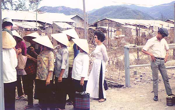14. Nha Trang AB Gate Post-4. Entry/Exit for Civilian Vietnamese workers.Women go thru the shack and are searched by a Chinese female. Vietnamese man waiting to be searched when leaving. Photo by: Tony Niemotka, LM 577, NT, 14th SPS, 1968-1969.