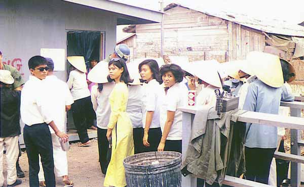 15. Nha Trang AB Gate Post-4. Civilian Vietnamese women go thru the shack and are searched by a Chinese female (Happy in their work?). Vietnamese man waiting to be searched when leaving. Photo by: Tony Niemotka, LM 577, NT, 14th SPS, 1968-1969.