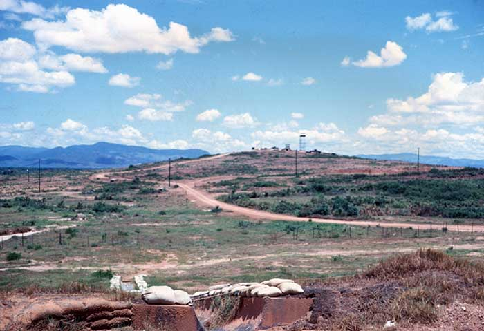 22. Standing on the west shoulder of the runway, looking west toward the Army outpost on the rise. Photo by Don Bishop. 1969-1970.