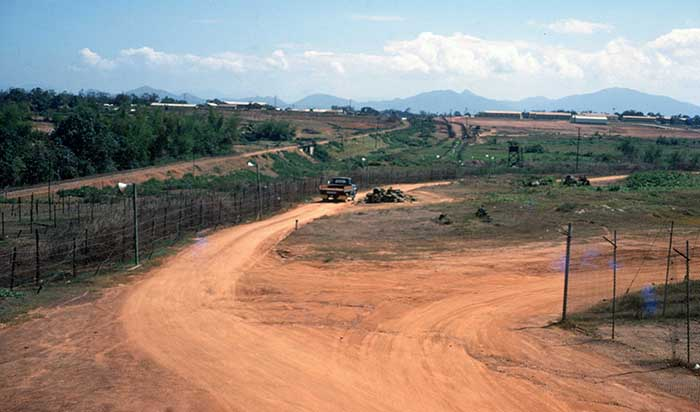 18. The Phu Cat AB perimeter on the east side of the base, from Tango 4 looking south. On the horizon: the ROK Army camp on the left, the base barracks on the right. From L to R: the Village adjacent to the base, the railroad, the physical perimeter (barbed wire, tanglefoot, belts of concertina, lights). The trip flares in the concertina are not visible. Supply yard fence to the right. Photo by Don Bishop. 1969-1970.