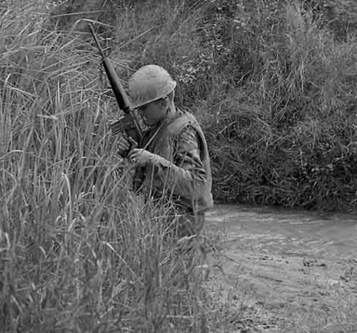 13. USAF SP crosses stream, searching for VC and NVA sappers. 600th Photo Squadron, Vietnam.