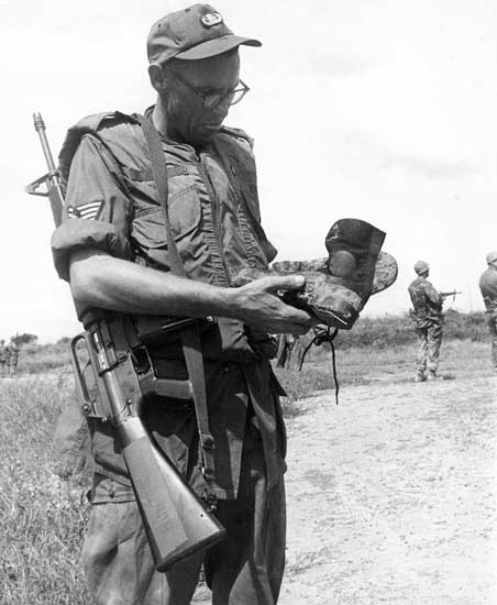 14. NCO examines VC boots, discarded while fleeing. 600th Photo Squadron, Vietnam.
