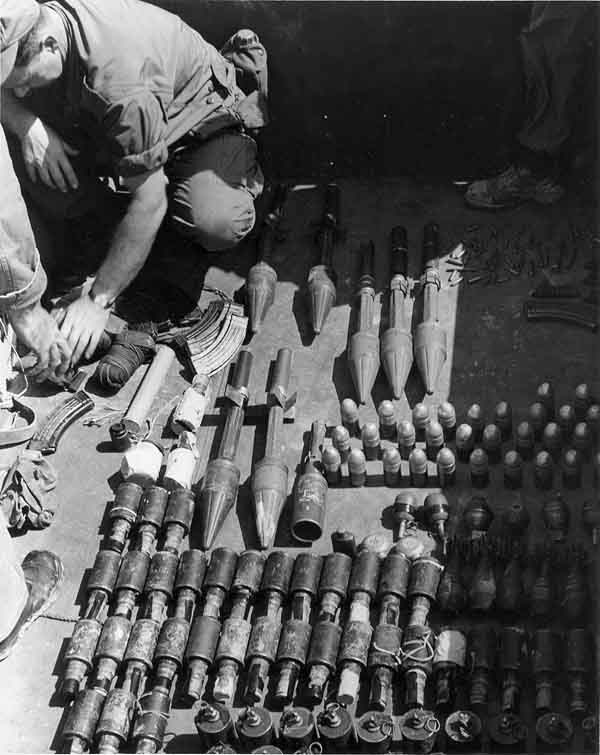 15. Photo right: SPSs check out VC/NVA weapons cache displayed. 600th Photo Squadron, Vietnam.