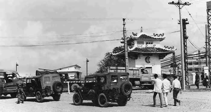 5. TSN AB: Main Gate. Jeeps and civilian workers line up to enter airbase. Photo by Roy F. Martin Jr.