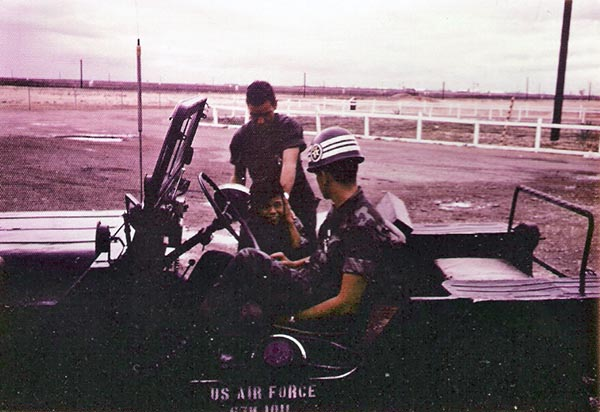 7. Tuy Hoa AB: Batman, Vietnamese boy, greets SPs. Photo by Sgt deWhite. 1969-1970.