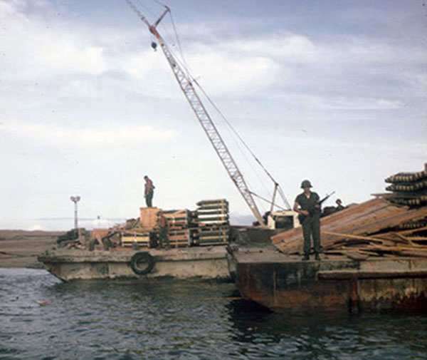 9. Tuy Hoa AB: 31st SPS, SP stands guard as bombs are unloaded. Photo by Ed Barker. 1966-1967.